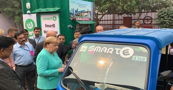 FILE PHOTO: German Chancellor Angela Merkel stands next to an electric vehicle during her visit