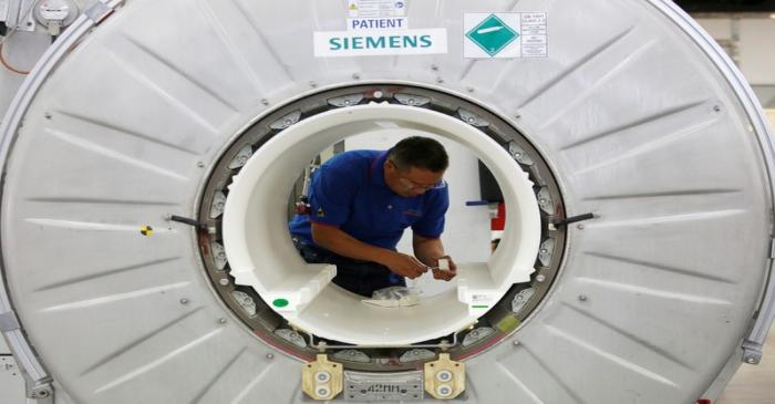 FILE PHOTO: A staffer works on a magnetic resonance imaging machine at a production line of