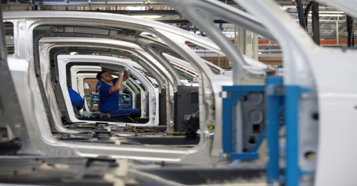 An employee works on the automobile assembly line of Bluecar electric city cars at Renault car