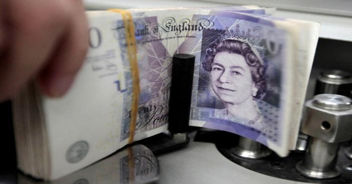 A bank employee counts pound notes at Kasikornbank in Bangkok