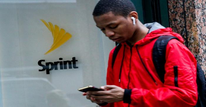 FILE PHOTO: A man walks past a Sprint store in New York
