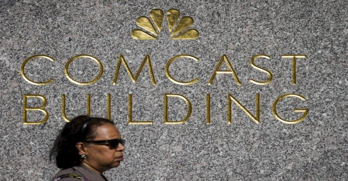 A woman walks past the NBC logo and Comcast at 30 Rockefeller Plaza in Manhattan, New York