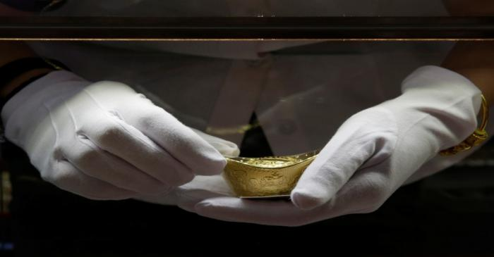 A sales assistant takes out a gold ornament for a customer at Caibai Jewelry store in Beijing