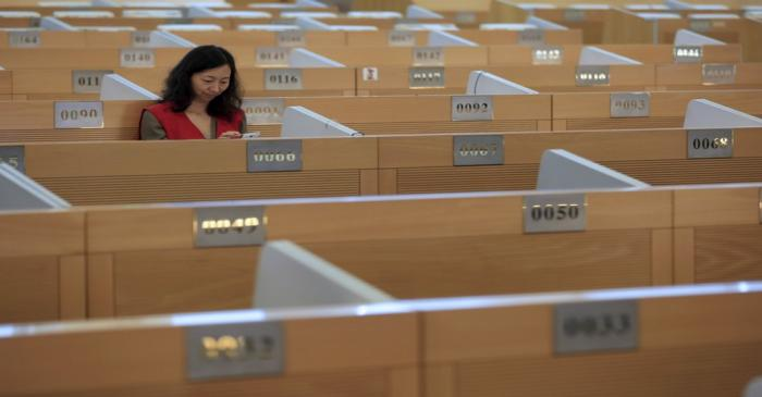 A trader checks her phone on the trading floor at the Shanghai Stock Exchange in Lujiazui