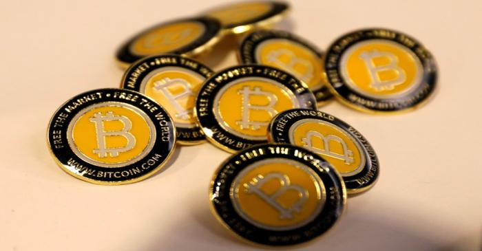 FILE PHOTO: Bitcoin.com buttons are seen displayed on the floor of the Consensus 2018