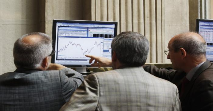 Traders look at a computer screen at the Madrid Bourse