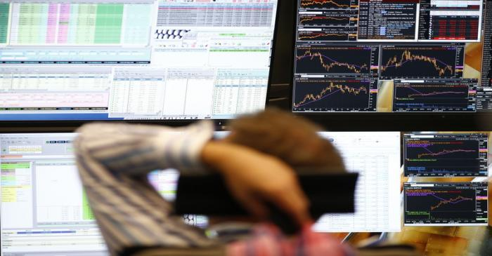 A trader sits in front of the computer screens at his desk at the Frankfurt stock exchange
