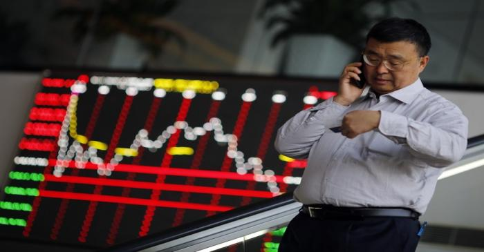 A man talks on the phone inside the Shanghai Stock Exchange building at the Pudong financial