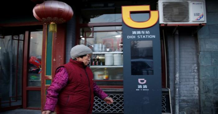 Woman walks past a sign of station for Didi Chuxing in Beijing