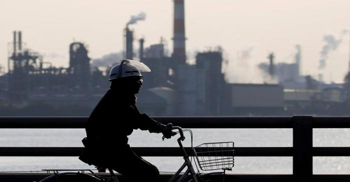 FILE PHOTO: A worker cycles near a factory at the Keihin industrial zone in Kawasaki, Japan