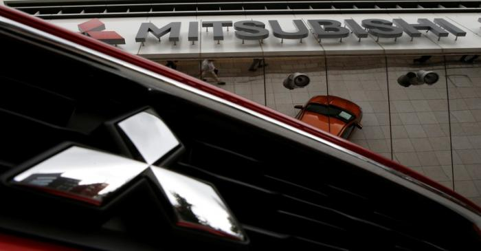 Mitsubishi Motors Corp's logo on a car and its company headquarters are seen in Tokyo