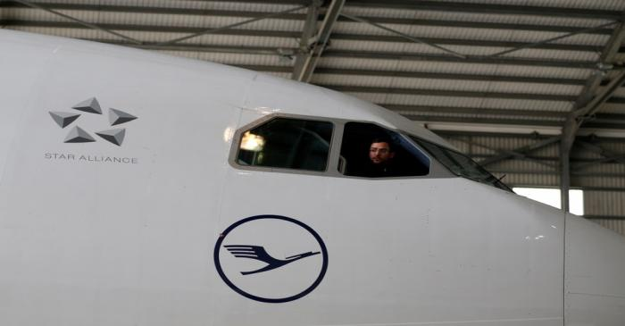 A technician looks out of the cockpit of a Lufthansa Airbus A330-300 aircraft in a maintenance