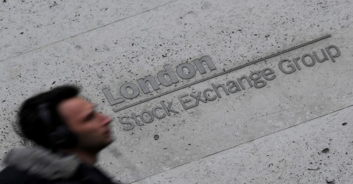 FILE PHOTO: A man walks past the London Stock Exchange Group offices in the City of London,