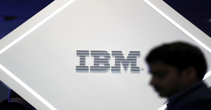 FILE PHOTO: A man stands near an IBM logo at the Mobile World Congress in Barcelona