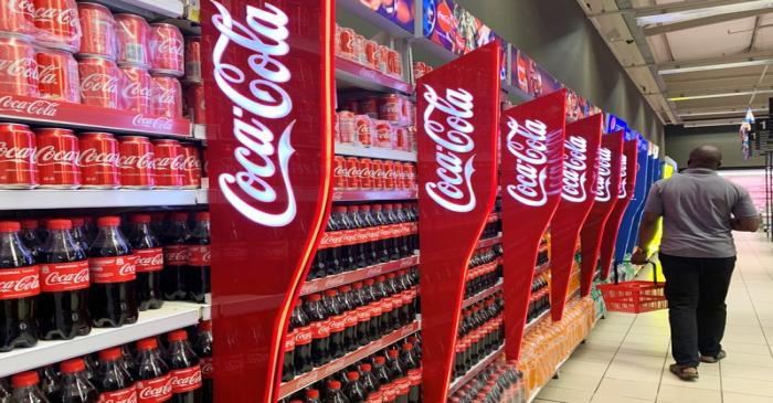 A man walks past shelves of Coca-Cola bottles and cans at a Shoprite store inside Palms