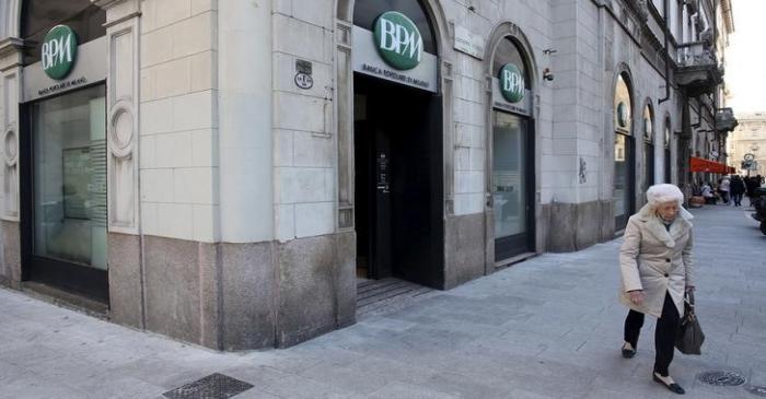 A woman walks past Banca Popolare di Milano ( BPM) downtown Milan
