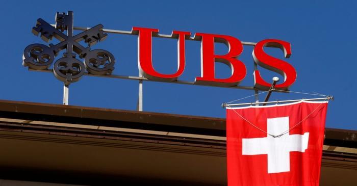 Switzerland's national flag flies under the logo of Swiss bank UBS in Zurich