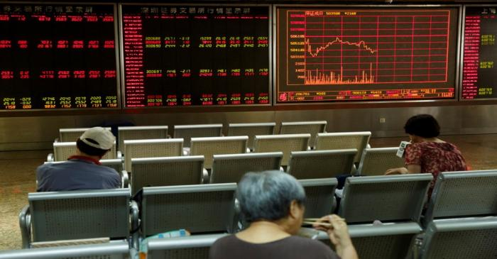 People sit in front of a board showing market information at a securities brokerage house in