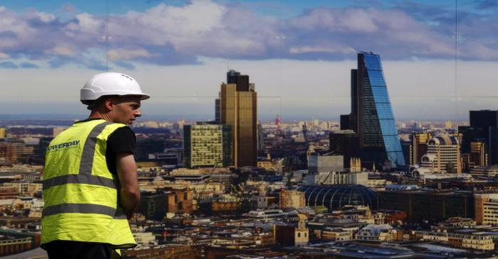 A worker walks past a picture of the London skyline outside the sales office of a property