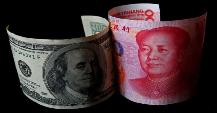FILE PHOTO: A 100 yuan banknote is placed next to a $100 banknote in this picture illustration