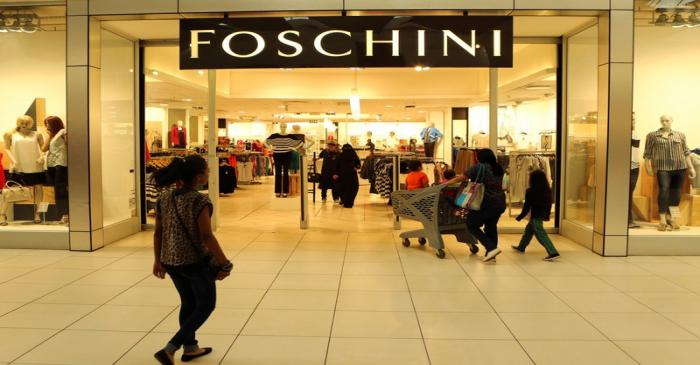 FILE PHOTO: A shopper walks past a Foschini store at a shopping centre in Lenasia, south of