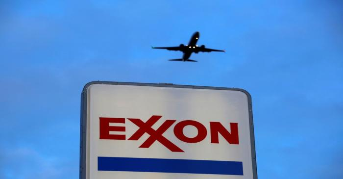 FILE PHOTO: An airplane comes in for a landing above an Exxon sign at a gas station in the