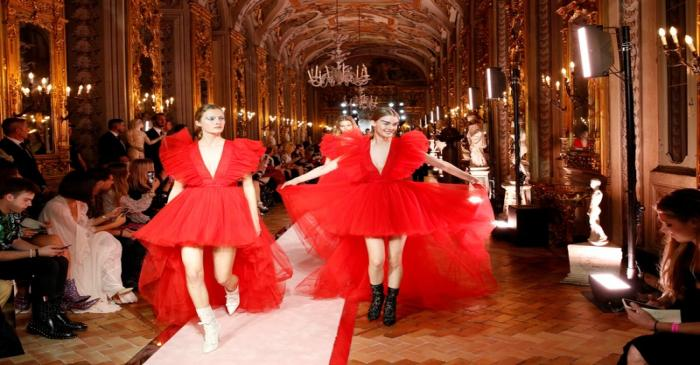 FILE PHOTO: Two models on the catwalk wear a red tulle plunge-v neck asymetrical dress, paired