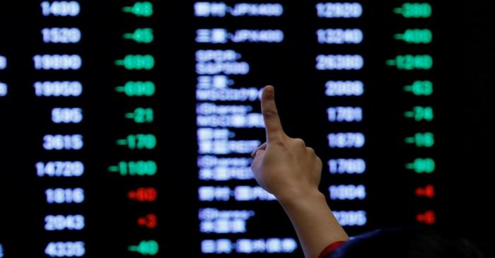 A woman points to an electronic board showing stock prices as she poses in front of the board