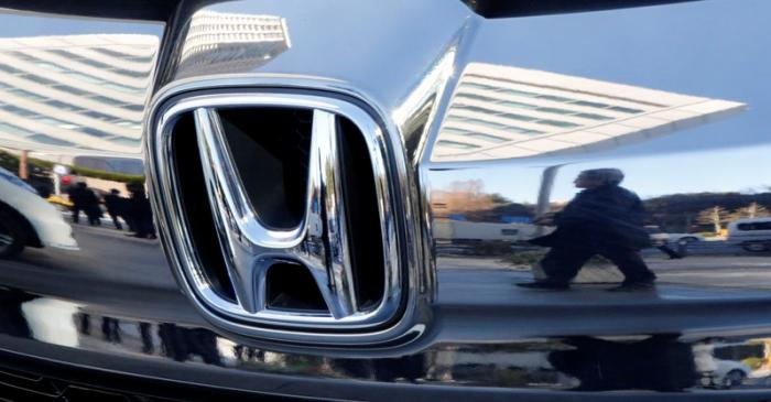 People are reflected on a Honda Motor car outside the company's headquarters in Tokyo
