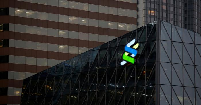 FILE PHOTO: A logo of Standard Chartered is displayed at the financial Central district in Hong