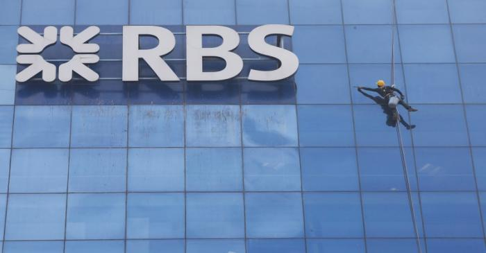 FILE PHOTO: Worker cleans the glass exterior next to the logo of RBS (Royal Bank of Scotland)
