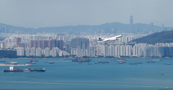 A Cathay Pacific flight flies over the city of Hong Kong