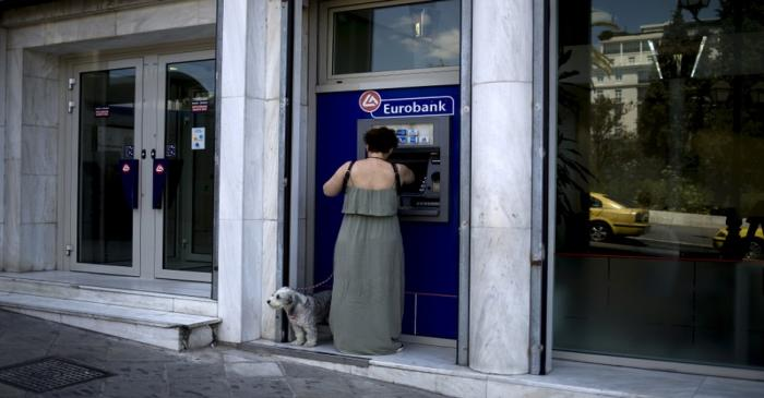 FILE PHOTO: Woman uses a Eurobank ATM in Athens