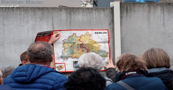 People watch a map of the divided West and East Berlin shown on remains of the Berlin Wall at