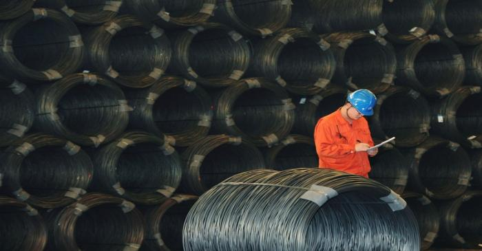 Employee works next to steel wires at a Dongbei Special Steel plant in Dalian