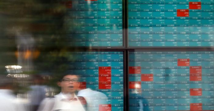A man is reflected on a stock quotation board outside a brokerage in Tokyo