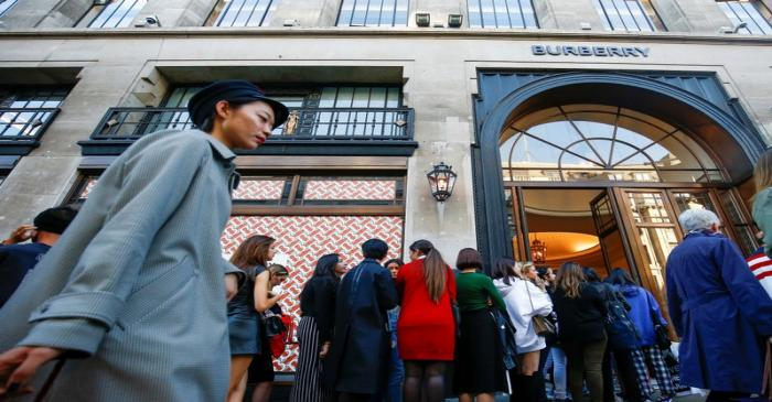 FILE PHOTO: People queue outside a Burberry store on Regent Street, London