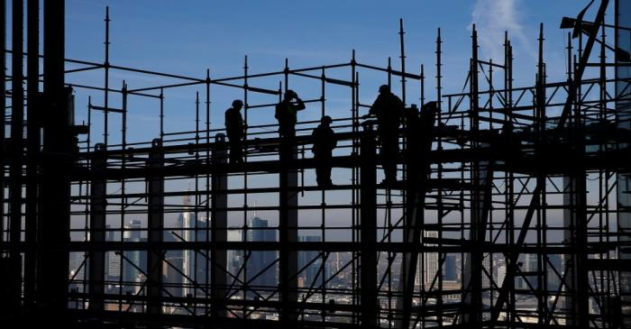 Construction workers are silhouetted while standing on scaffolding at the construction site of