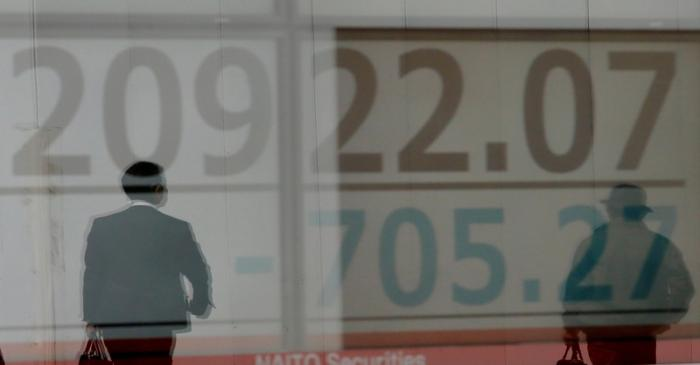 Men are reflected on an electronic board showing the Nikkei stock index outside a brokerage in