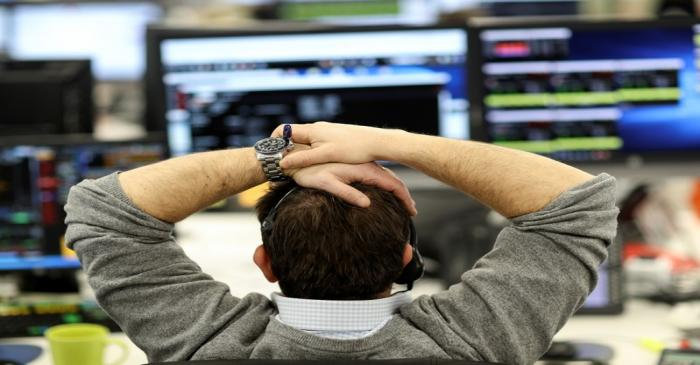A broker looks at financial information on computer screens on the IG Index trading floor