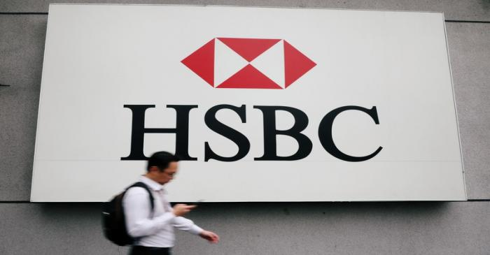 A man walks past a logo of HSBC at its headquarters in Kuala Lumpur