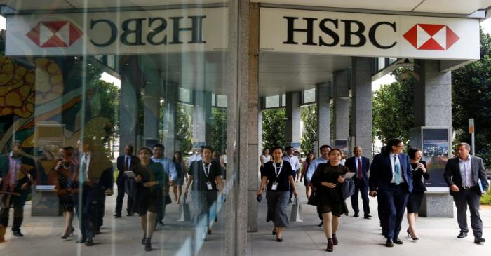 People walk past a HSBC signage in Singapore
