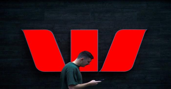FILE PHOTO: A pedestrian looks at his phone as he walks past a logo for Australia's Westpac