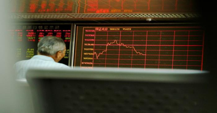 A man sits in front of a board showing market information at a securities brokerage house in