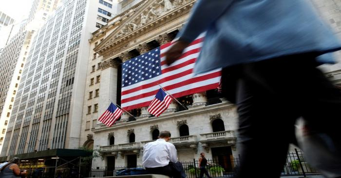 FILE PHOTO: People sit outside the NYSE during the morning commute