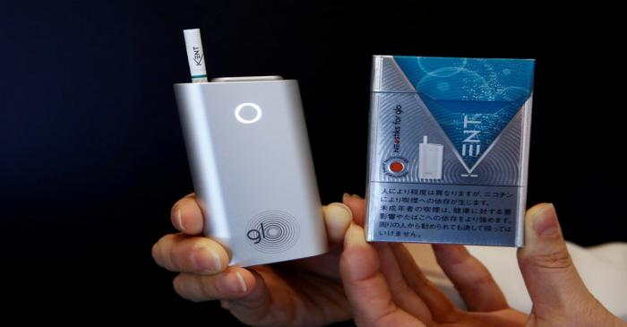 FILE PHOTO: A promoter shows British American Tobacco's new tobacco heating system device 'glo'