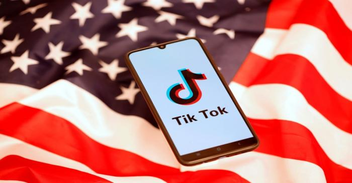 FILE PHOTO: TikTok logo is displayed on the smartphone while standing on the U.S. flag in this