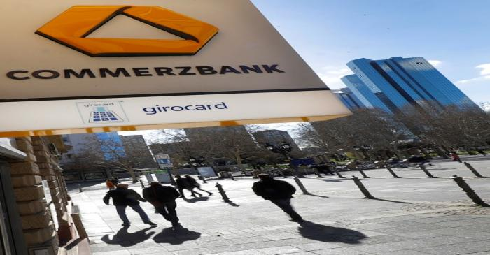 FILE PHOTO: A sign for an ATM of Commerzbank is seen next to the headquarters of Deutsche Bank