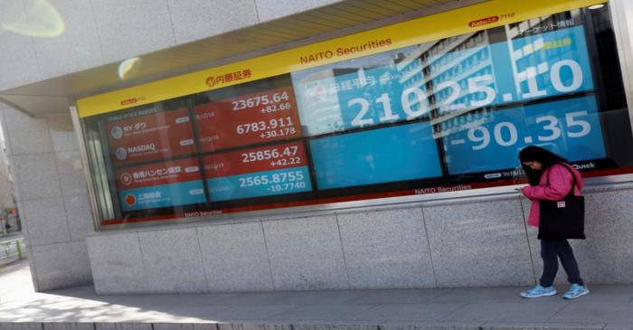 A woman stands in front of a screen displaying Japan's Nikkei share average, U.S. and other