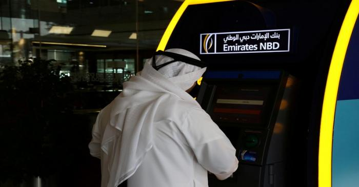 FILE PHOTO: A customer uses an ATM machine at the Emirates NBD head office in Duba